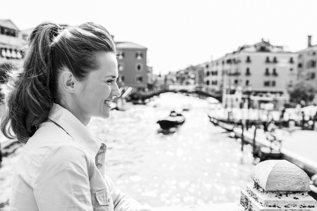 Her hair swept up in a ponytail, this elegant tourist smiles as she looks off into the distance. In the background, Venices rich colors and one of its many canals.