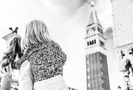 Mother and baby looking on campanile di san marco in venice, italy