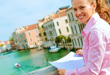 happy young woman with map standing on bridge with grand canal view in venice, italy