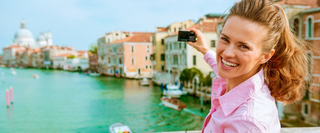 Happy young woman standing on bridge with grand canal view in venice, italy and taking photo