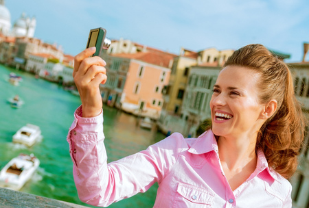 Happy young woman standing on bridge with grand canal view in venice, italy and taking self photo