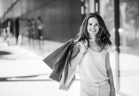 Portrait of happy young woman with shopping bags on the mall alley