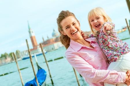 happy mother and baby on grand canal embankment in venice, italy Stock Photo