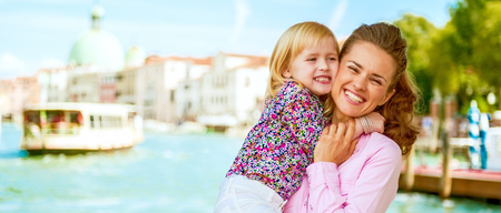 happy mother and baby hugging on grand canal embankment in venice, italy Stock Photo