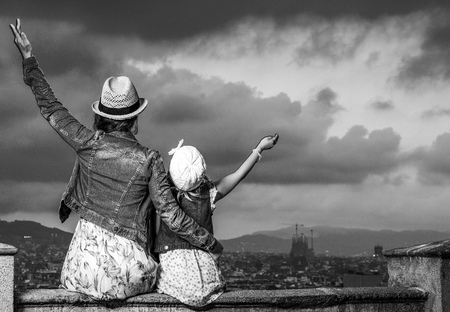 Perfect evening with stunning view. Seen from behind trendy mother and child travellers against cityscape of Barcelona, Spain rejoicing Stock Photo