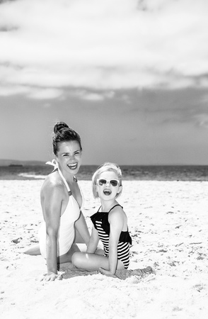 Family fun on white sand. happy young mother and child in beachwear sitting on the seacoast Stock Photo
