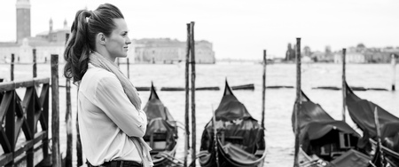 A woman stands, dreaming of times past, listening to the sound of the water lapping against the moored gondolas.