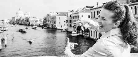 Happy young woman framing with hands while standing on bridge with grand canal view in venice, italy