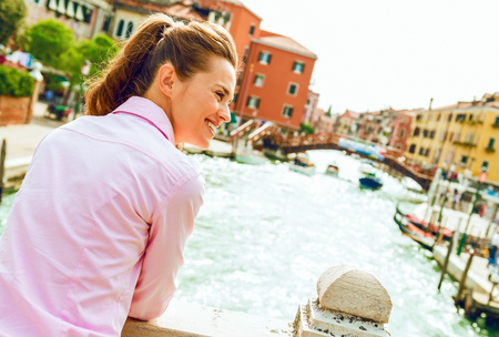 Happy young woman standing on bridge in venice, italy and looking on copy space