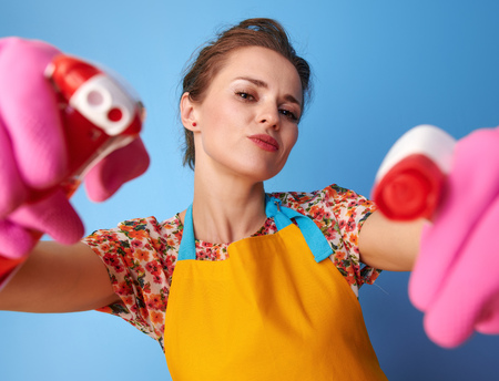 Big cleaning time. cool young housewife with rubber gloves using bottles of cleaning detergent as guns isolated on blue Фото со стока