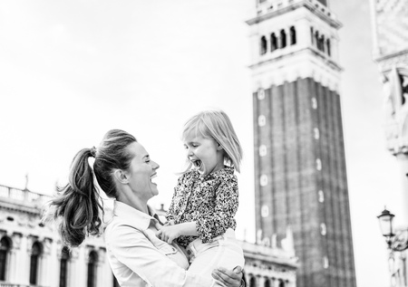 Portrait of smiling mother and baby against campanile di san marco in venice, italy