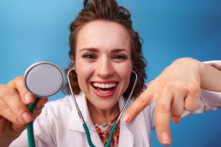 happy pediatrician doctor in white medical robe using stethoscope while distracting child playing isolated on blue