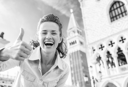 Happy young woman against campanile di san marco showing thumbs up in venice, italy