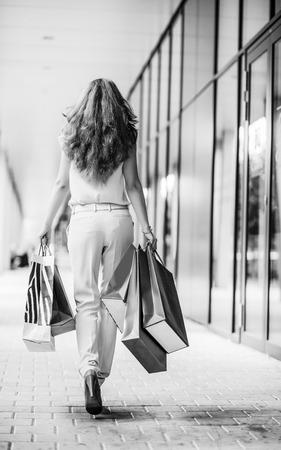 Young woman with shopping bags walking on the mall alley. rear view Stock Photo