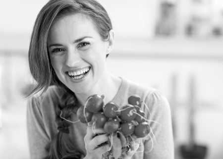Portrait of smiling young woman with bunch of radishes Stok Fotoğraf