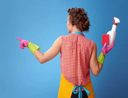 Big cleaning time. Seen from behind modern woman with rubber gloves and kitchen sponge and a bottle of detergent pointing at something isolated on blue Stock Photo