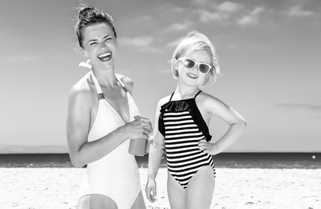 Family fun on white sand. happy young mother and daughter in swimsuit on the seacoast applying sun block Stock Photo
