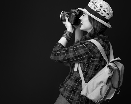 Searching for inspiring places. smiling adventure tourist woman with backpack and DSLR camera taking photo isolated on