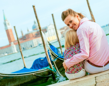 happy mother and baby sitting on grand canal embankment in venice, italy Stock Photo