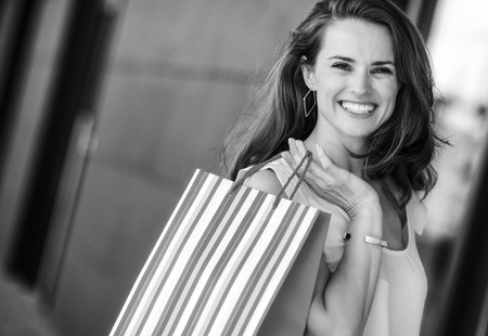 A brown-haired woman is seen from the waist up. She holds a striped, multi-coloured and shopping bag over her right shoulder. Her smile is relaxed and happy. She is effortlessly stylish and classic. Her wide smile make her approachable, happy, and warm. The sunlight plays on her face and hair, highlighting honey tones and the gold bangle on her arm. Imagens