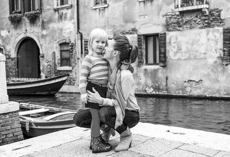 My mommy is the best, thinks this little girl, as her mother nuzzles her lovingly as she is kneeling down next to her. Stockfoto