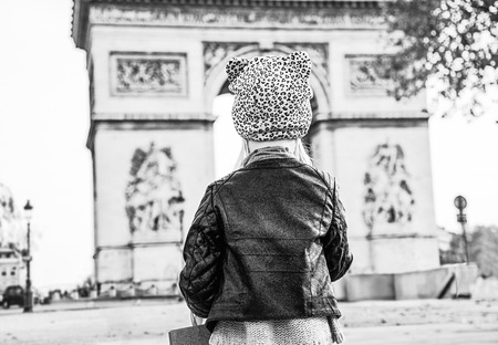 Stylish autumn in Paris. Seen from behind modern child in Paris, France