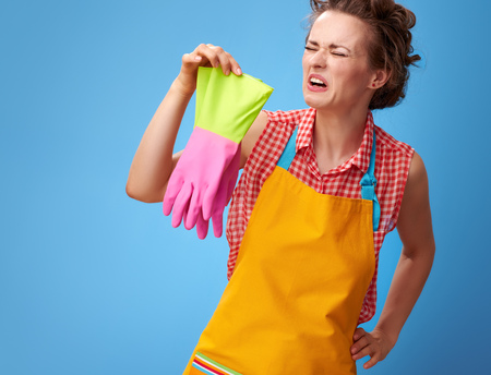 Big cleaning time. sad young housewife in a yellow apron sniffing rubber gloves isolated on blue