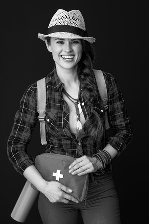 Searching for inspiring places. smiling active traveller woman in a plaid shirt with first-aid kit isolated on background Stock Photo
