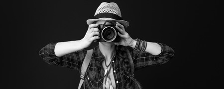 Searching for inspiring places. adventure traveller woman in a plaid shirt with digital camera taking photo on background