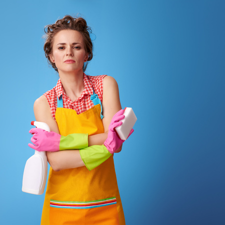 Big cleaning time. Cool young woman in a yellow apron with kitchen sponge and cleaning detergent against blue background Stok Fotoğraf