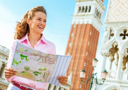 Happy young woman looking at map against campanile di san marco in venice, italy