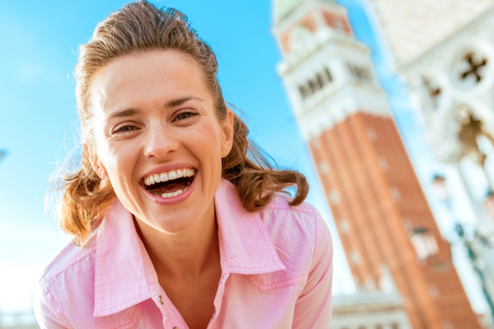 happy young woman against campanile di san marco in venice, italy