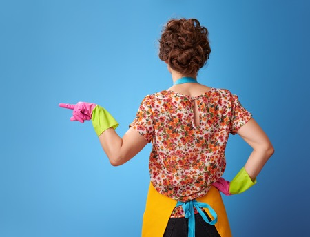 Big cleaning time. Seen from behind modern woman in a yellow apron pointing at something isolated on blue