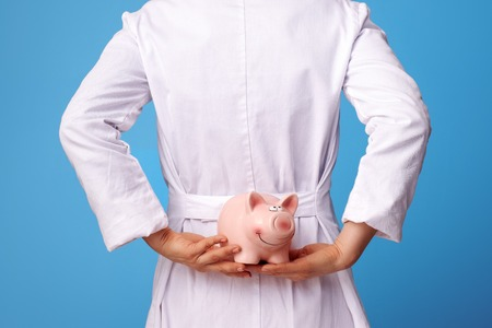 Closeup on medical doctor woman in white medical robe holding piggybank behind back isolated on blue background