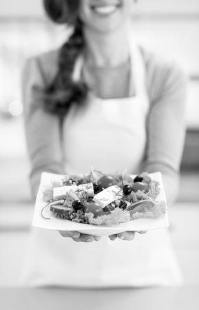 Closeup on young housewife showing greek salad Banco de Imagens