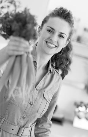 Happy young housewife giving bunch of carrots Stockfoto