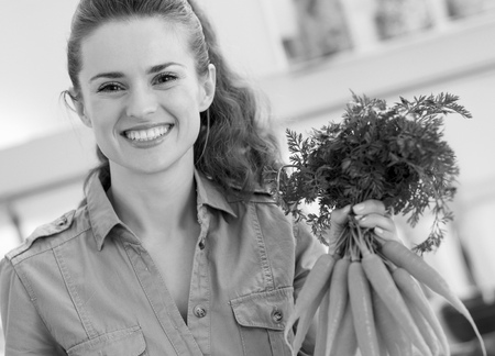 Happy young housewife holding bunch of carrots in kitchen Фото со стока