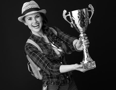 Searching for inspiring places. happy active traveller woman in a plaid shirt showing goblet on background