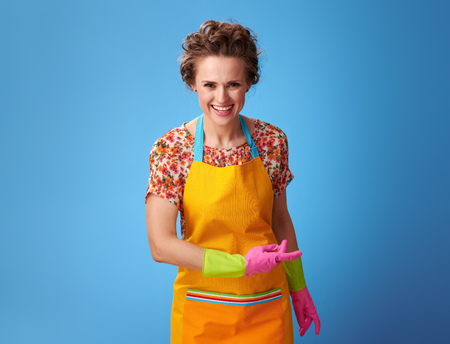 Big cleaning time. smiling young woman with rubber gloves bowing isolated on blue background