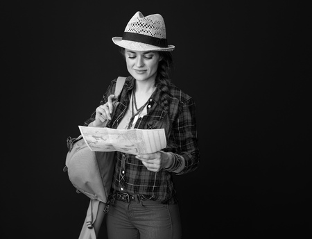 Searching for inspiring places. healthy traveller woman in a plaid shirt looking at the map isolated on