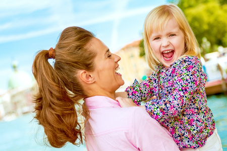 Discovering new places together is just the best, isnt it? Here, a mother lovingly holds her daughter, laughing at how silly and happy her daughter is being while she holds her in her arms.