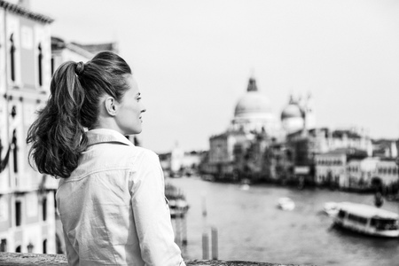 Young woman looking into distance while standing on bridge with grand canal view in venice, italy