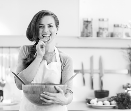 Happy young housewife tasting slice of cucumber from vegetable salad