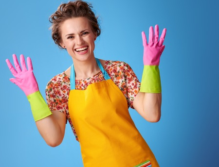 Big cleaning time. smiling modern woman showing rubber gloves isolated on blue background