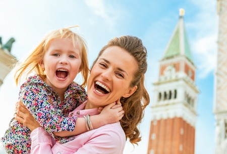 happy mother and baby against campanile di san marco in venice, italy