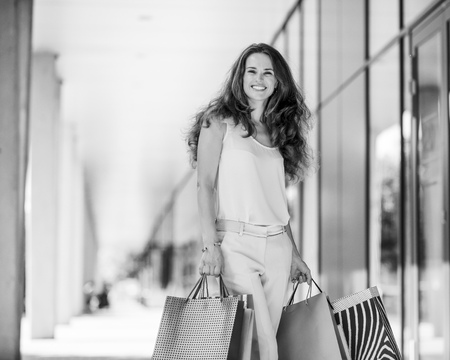 A brown-haired woman wearing muted, gentle shades holds five colourful, patterned shopping bags during a successful shopping spree. Walking outside, she is enjoying the warmth of a summer day. Her smile is confident and happy. Shopping at exclusive shops, this woman is stylish and elegant. Banco de Imagens