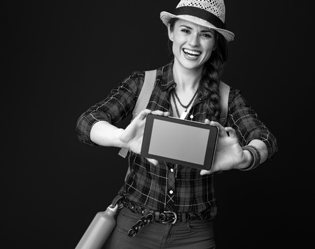 Searching for inspiring places. happy active woman hiker in a plaid shirt showing tablet PC blank screen isolated on