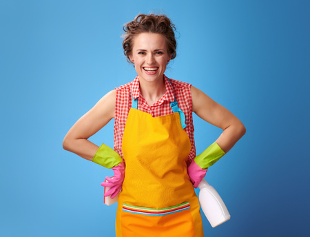 Big cleaning time. happy modern woman in a yellow apron with kitchen sponge and cleaning detergent isolated on blue Stock Photo