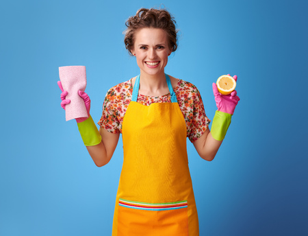 Big cleaning time. smiling young housewife with rubber gloves holding half a lemon and cleaning cloth isolated on blue background Foto de archivo
