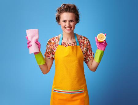 Große Reinigungszeit. lächelnde junge Hausfrau mit Gummihandschuhen, die eine halbe Zitrone und Reinigungstuch lokalisiert auf blauem Hintergrund halten Standard-Bild